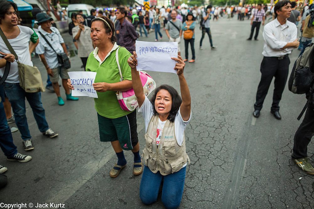 26 MAY 2014 - BANGKOK, THAILAND: A man kneels on the roadway on Phaya Thai Road during a protest against the coup in Thailand at Victory Monument during a pro-democracy rally in Bangkok. About two thousand people protested against the coup in Bangkok. It was the third straight day of large pro-democracy rallies in the Thai capital as the army continued to tighten its grip on Thai life.   PHOTO BY JACK KURTZ