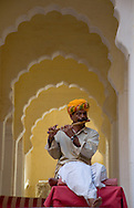 A man in traditional Indian dress playing a wooden flute at the Mehrangarh Fort in <br /> Jodhpur, Rajasthan, India