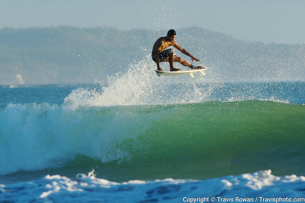 "Professional Balinese surfer, ""Bol"" performs an aerial maneuver on Bali's Kuta beach."