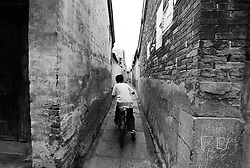 Very narrow alleyway between two houses in a Beijing hutong