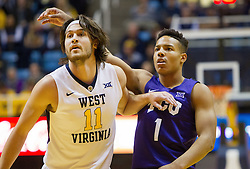 Jan 7, 2017; Morgantown, WV, USA; TCU Horned Frogs guard Desmond Bane (1) shoots a three pointer over West Virginia Mountaineers forward Nathan Adrian (11) during the first half at WVU Coliseum. Mandatory Credit: Ben Queen-USA TODAY Sports
