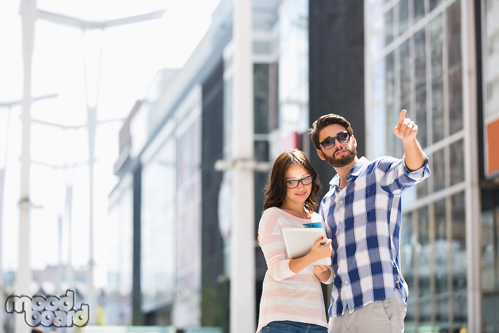 Man pointing while woman using digital tablet outside building