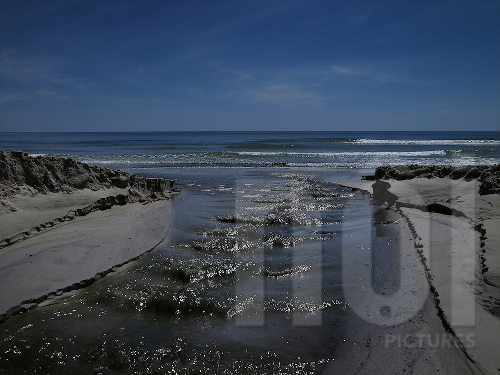 Water swiftly flows along the beach into the ocean, Dong Hoi, Quang Binh Province, Vietnam, Southeast Asia