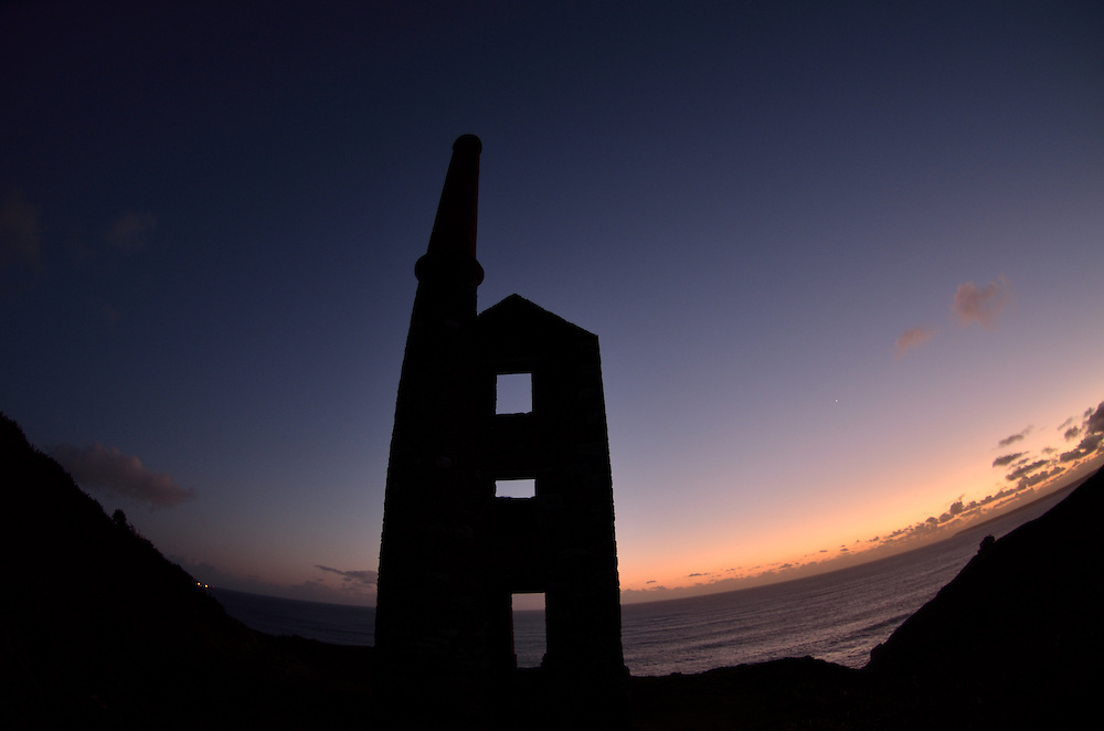 Wheal Prosper as the sunsets in Cornwall.<br /> <br /> Despite its name Wheal Prosper was not a hugely succesful mine, working for only six years between 1860-1866. It was intended to mine tin and copper from the Porthcew Lode<br /> <br /> The engine house is dramatically situated on the cliff tops of Rinsey over-looking Rinsey Cove and Porthcew Beach 3 miles from Portleven. Built of granite and killas slate taken from the local clifftops this fine engine house was home to a 30 inch pump.<br /> <br /> There were 3 shafts most notable of which is the now capped Michell's Whim shaft measuring an estimated 420ft in depth.<br /> <br /> The site has been under the stewardship of the National Trust since 1969.
