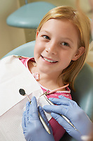 Girl (7-10) at dentists (close-up)