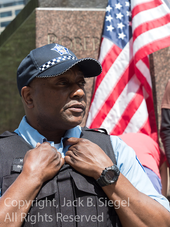 A member of the Chicago Police Department is standing ready, acting as a human barricade between the anti-Sharia law protesters and the anti-Trump protesters