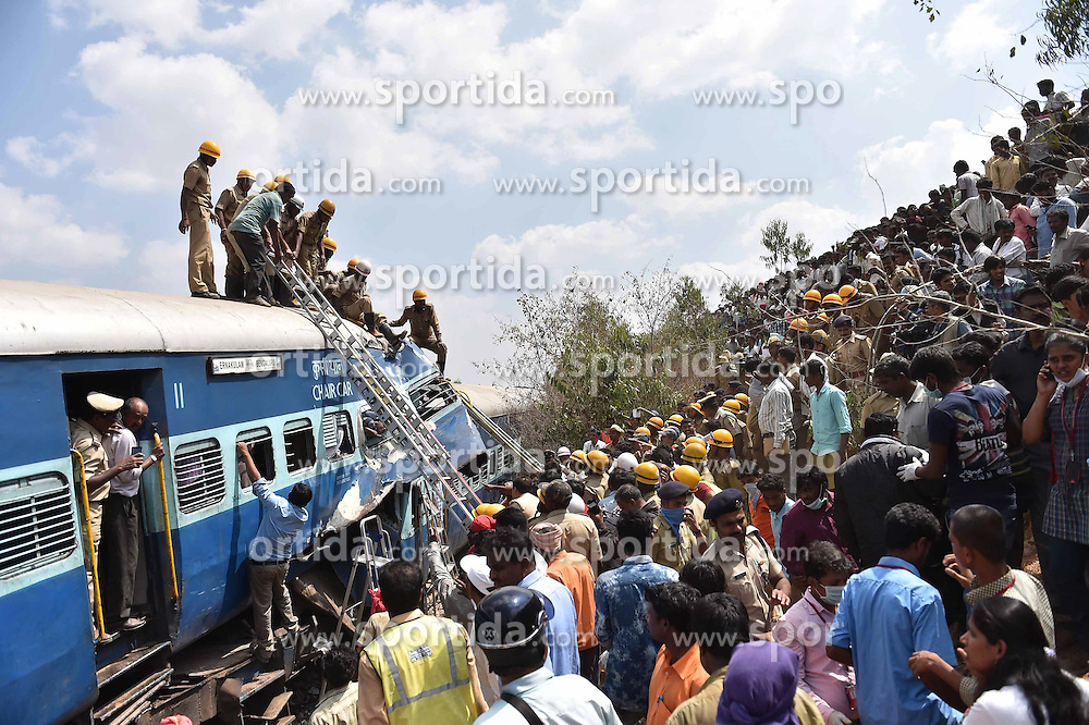 Crowds watch as rescuers cut the outer shell of a crumbled compartment of a derailed train to pull out the body of a victim near Anekal, about 40 kilometers south of Bangalore, India, Feb. 13, 2015. At least 12 people were killed and more than 150 others injured in a train derailment in the southern Indian state of Karnataka on Friday, a senior police officer said. EXPA Pictures © 2015, PhotoCredit: EXPA/ Photoshot/ Stringer<br /> <br /> *****ATTENTION - for AUT, SLO, CRO, SRB, BIH, MAZ only*****