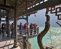 Tourists take advantage of a pagoda-style deck to photograph the Yangtze River as it flows between Jingzhou and Chongqing. Site is a re-created traditional water village at Hama Spring on Mingyue Bay, a shore excursion for Yangtze River cruises.