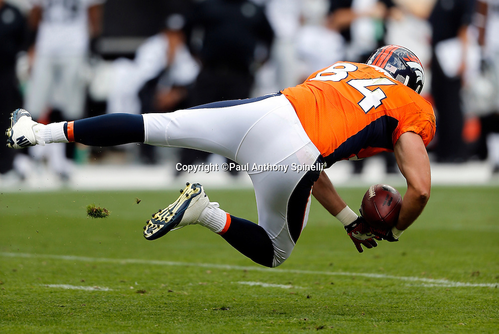 Denver Broncos tight end Jacob Tamme (84) gets upended after catching a first quarter pass during the NFL week 4 football game against the Oakland Raiders on Sunday, Sept. 30, 2012 in Denver. The Broncos won the game 37-6. ©Paul Anthony Spinelli