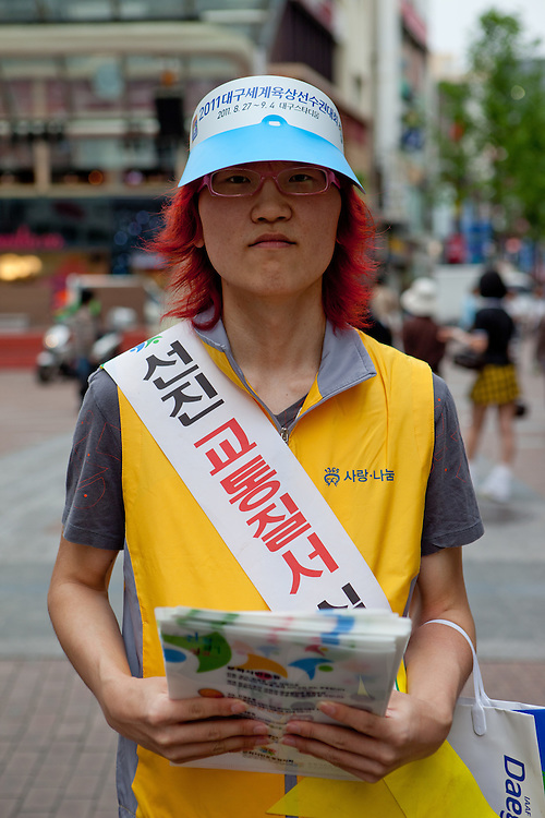 Portrait of a student working as a volunteer to promote the event in Daegu. Daegu, also known as Taegu and officially the Daegu Metropolitan City, is the third largest metropolitan area in South Korea, and by city limits, the fourth largest city with over 2.5 million people. The IAAF World Championships in Athletics will take place in Daegu from the 27th of August till the 4th of September 2011.