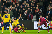 Granit Xhaka (Arsenal) falls backwards over Mark Noble (Capt) (West Ham) during the Premier League match between West Ham United and Arsenal at the London Stadium, London, England on 9 December 2019.