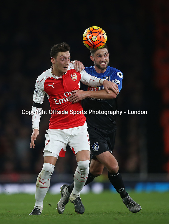 28 December 2015 - Premier League - Arsenal v AFC Bournemouth :<br /> Mesut Ozil holds off a challenge from Andrew Surman.<br /> Photo: Mark Leech
