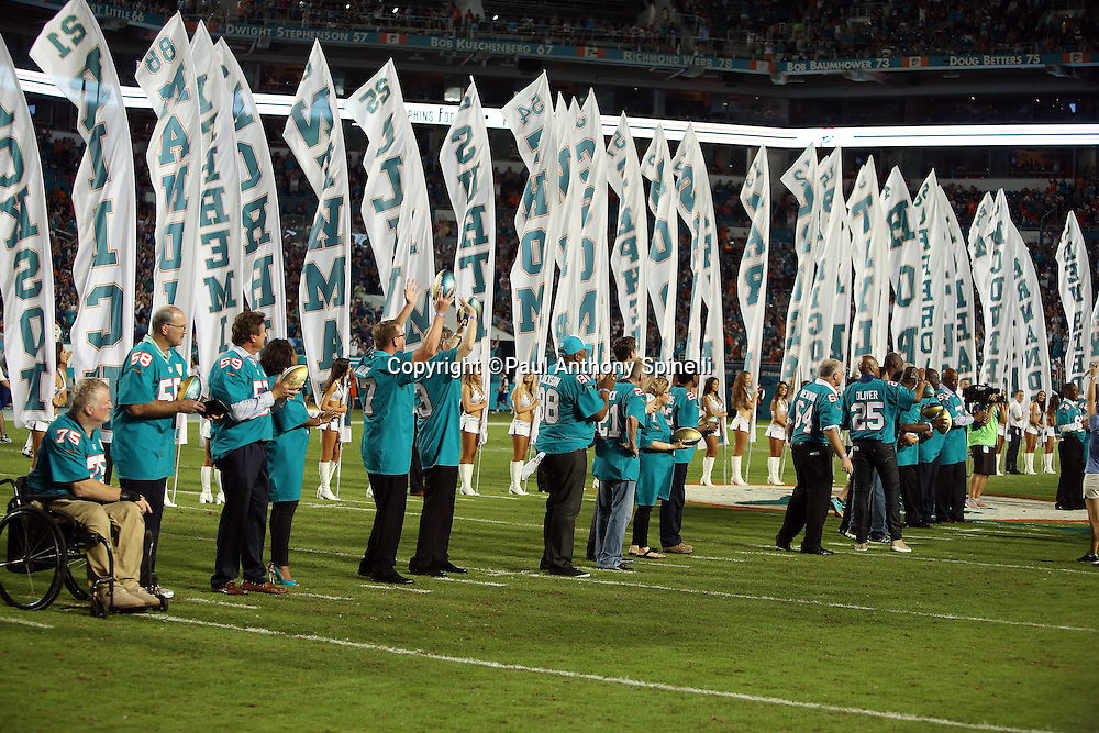 Former members of the Miami Dolphins are honored with footballs and banners during a halftime promotion honoring the top 50 players in franchise history during the NFL week 14 regular season football game against the New York Giants on Monday, Dec. 14, 2015 in Miami Gardens, Fla. The Giants won the game 31-24. (©Paul Anthony Spinelli)