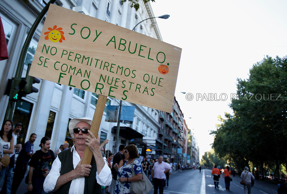 A protesters holds a placards that says (I am a  grandfather. We won't allow them to eat our flowers) in Madrid on October 15, 2011 during a protest against the global economic crisis. Organisers claim 950 protests held in over 80 countries. Spain.
