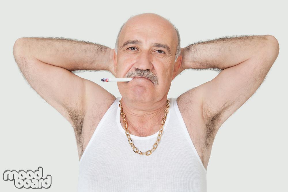 Portrait of senior man in vest smoking cigarette over gray background
