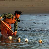 SHINIUJU, OCTOBER-26a man fishes in the Yalu river that divides China and North Korea in Shiniuju,October 26,2006.