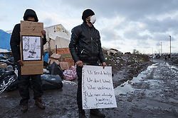 © London News Pictures. Calais, France. 07/03/16. Two Iranian men currently on hunger strike stand with signs as police enter the 'Jungle' camp. French authorities are evicting and demolishing the southern half of the Calais 'Jungle' camp, which charities estimate to contain 3,500 people. . Photo credit: Rob Pinney/LNP