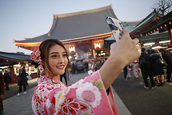 December 17, 2018 - Tokyo, Japan - A Chinese tourist dressed in Japanese kimono poses for a selfie at the Sensoji Temple in Asakusa district. This year the number of foreign tourists visiting Japan is expected to exceed 30 million for the first time ever, according the Japanese tourist agency. The government has set a target to attract 40 million overseas tourists in 2020, the year of the Tokyo Olympic Games. (Credit Image: © Rodrigo Reyes Marin/ZUMA Wire)