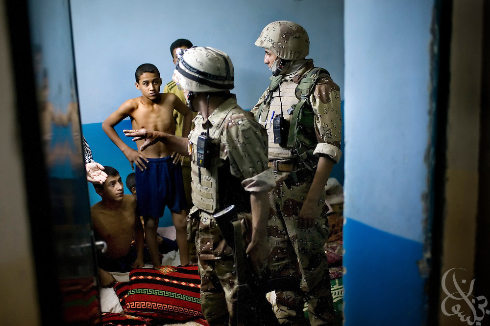 Iraqi Army 2nd Division soldiers explain to the family of a suspected terrorist financier that they are taking the man into custody during a raid October 18, 2007 in Mosul, Iraq. Iraqi security forces in Mosul have taken over the day to day tasks of securing the city, allowing U.S. forces in the area to pull back and reduce its presence.
