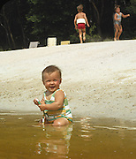 8 month old girl sitting in shallow water of lake