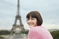 France Paris Young woman smiling with Eiffel Tower in distance