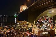 Nederland, Nijmegen, 16-7-2014 Recreatie, ontspanning, cultuur, dans, theater en muziek in de binnenstad tijdens de zomerfeesten. Het alternatieve en relaxte terrein onder de Waalbrug van festival de Kaaij waar eten en drinken, verschillende soorten live muziek en zitten bij het water van de rivier de Waal de leukste dingen zijn. Een van de tientallen feestlocaties in de stad. Onlosmakelijk met de vierdaagse, 4daagse, zijn in Nijmegen de vierdaagse feesten, de zomerfeesten. talrijke podia staat een keur aan artiesten, voor elk wat wils. Een week lang elke avond komen tegen de honderdduizend bezoekers naar de stad. De politie heeft inmiddels grote ervaring met het spreiden van de mensen, het zgn. crowd control.De vierdaagsefeesten zijn het grootste evenement van Nederland en verbonden met de wandelvierdaagse. Foto: Flip Franssen/Hollandse Hoogte