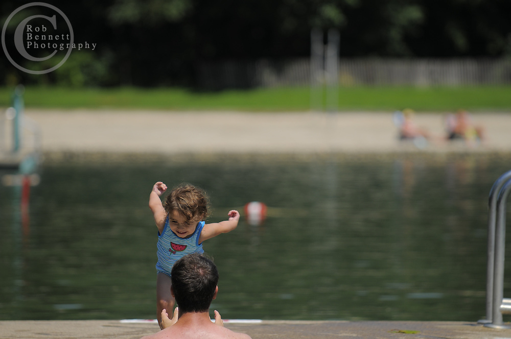 "here, Ellie Sklar (2.5 y.o.) leaps into the arms of her father, Brett Sklar.---.Ridgewood, NJ /  Sun, Aug 30, 2009:.Graydon Pool, Ridgewood, NJ.Suzanne Kelly.Marcia Ringel.-the 2 organizers who are trying to save the pool .-scenes of people having fun at the town pool showing how unique this town pool is since it looks more like a natural lake with sand beach, trees etc...Doing towns for Thursday next week from Ridgewood, NJ/ on fight over  beloved local park and swimming pool:..Here's summary: .Have you ever seen Graydon, the 2.5-acre pool in the middle of town? It's really a manmade, springfed pond, not a pool, surrounded by  sandy beaches, lawns, oak and cottonwood shade trees, with white wooden lifeguard stands, rafts, diving boards, etc. For decades it's been the village's jewel, the one distinctive thing everybody talks about..Now a group wants to plow it under and convert it to a.country-club-style concrete complex with waterpark features. No more pond, no more sand. They think the existing pond is too natural -- and too ""dirty"" since the water isn't clear and chlorinated. They have raised a bunch of money and done some studies, all very biased, and  are pushing the village council to spend $10 million or more. It looked like the thing was going to be ramrodded through when about three weeks ago a woman named Suzanne Kelley, starting as what  she called a coalition of one, stood up and said stop. She started  gathering signatures among people who either like the pond the way it is or think it's crazy during these tough times to spend $10 million to fix something that ain't broke. And they think the concrete pool .faction wants something snootier and just for Ridgewood folks, instead of current one which  allows neighboring towns and would cost half as much in membership dues as the proposed new one......Suzanne Kelly and Marcia Ringel.Co-Chairs, The Preserve Graydon Coalition..www.preservegraydon.org.---.Rob Bennett for The New York Times"