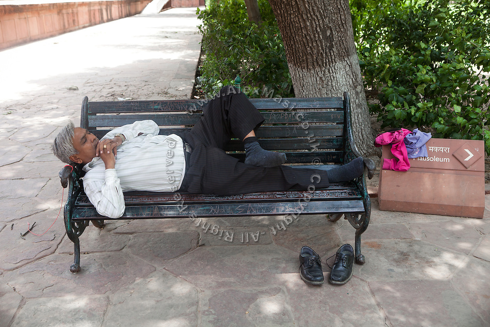 A man is taking a nap on a bench inside the Taj Mahal complex, in Agra.