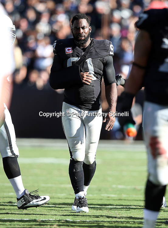 Oakland Raiders defensive end Justin Tuck (91) walks near the sideline with his arm in a sling during the 2015 NFL week 5 regular season football game against the Denver Broncos on Sunday, Oct. 11, 2015 in Oakland, Calif. The Broncos won the game 16-10. (©Paul Anthony Spinelli)