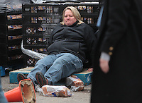 Leslie Miller sits on the ground after being hit by a car during the Second Harvest Food Giveaway Wednesday morning. Another man was taken to Ball Memorial Hospital with a possible broken leg.  .(Chris Bergin/ The Star Press)