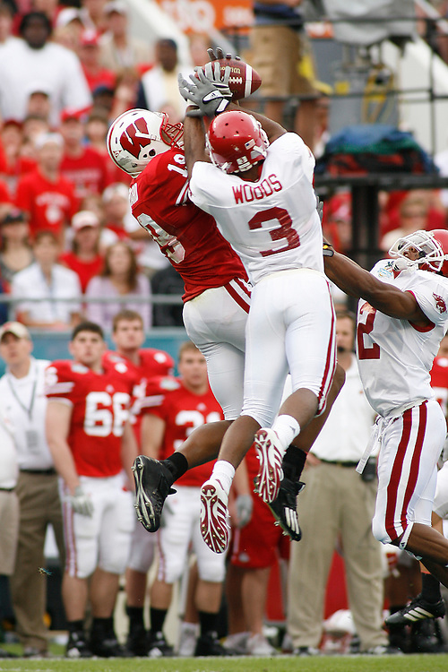 University of Wisconsin wide receiver Paul Hubbard reaches over the hands of University of Arkansas defensive back Kevin Woods to make the catch during the Wisconsin Badgers 17-14 victory over the Arkansas Razorbacks on January 1, 2007 at the Florida Citrus Bowl Stadium in Orlando, Florida.