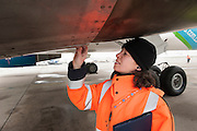 Nesrine, an aircraft inspector checks loose plates of a plane. At Roissy, Nesrine, 34, works as a technical inspector  for the DGCA (Directorate General of Civil Aviation) - she is the only female technical controller at the airport of Roissy-en-France. She can stop a Boeing taking off and make the 300 passengers leave the airplane. Nesrine Chkioua is the only woman controller at Roissy Airport and one of three women doing this job in France.<br /> <br /> <br /> &Agrave; Roissy, Nesrine, 34 ans, exerce le m&eacute;tier de contr&ocirc;leur technique (CTE) pour la DGAC (Direction g&eacute;n&eacute;rale de l&rsquo;aviation civile) - elle est la seule femme contr&ocirc;leur technique &agrave; l&rsquo;a&eacute;roport de Roissy-en-France.  Elle peut immobiliser un Boeing, retarder le d&eacute;collage et m&ecirc;me faire d&eacute;barquer les 300 passagers d&rsquo;un long-courrier. Nesrine Chkioua est la seule contr&ocirc;leur femme &agrave; Roissy a&eacute;roport et est une des trois femmes &agrave; exercer ce m&eacute;tier en France.