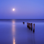 The full moon rising and its reflection run parallel to a line of poles consumed by the rising tide.
