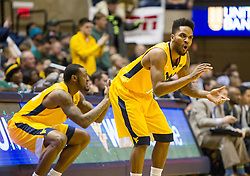 Feb 6, 2016; Morgantown, WV, USA; West Virginia Mountaineers guard Tarik Phillip (12) and forward Elijah Macon (45) celebrate at the scorers table during the first half against the Baylor Bears at the WVU Coliseum. Mandatory Credit: Ben Queen-USA TODAY Sports