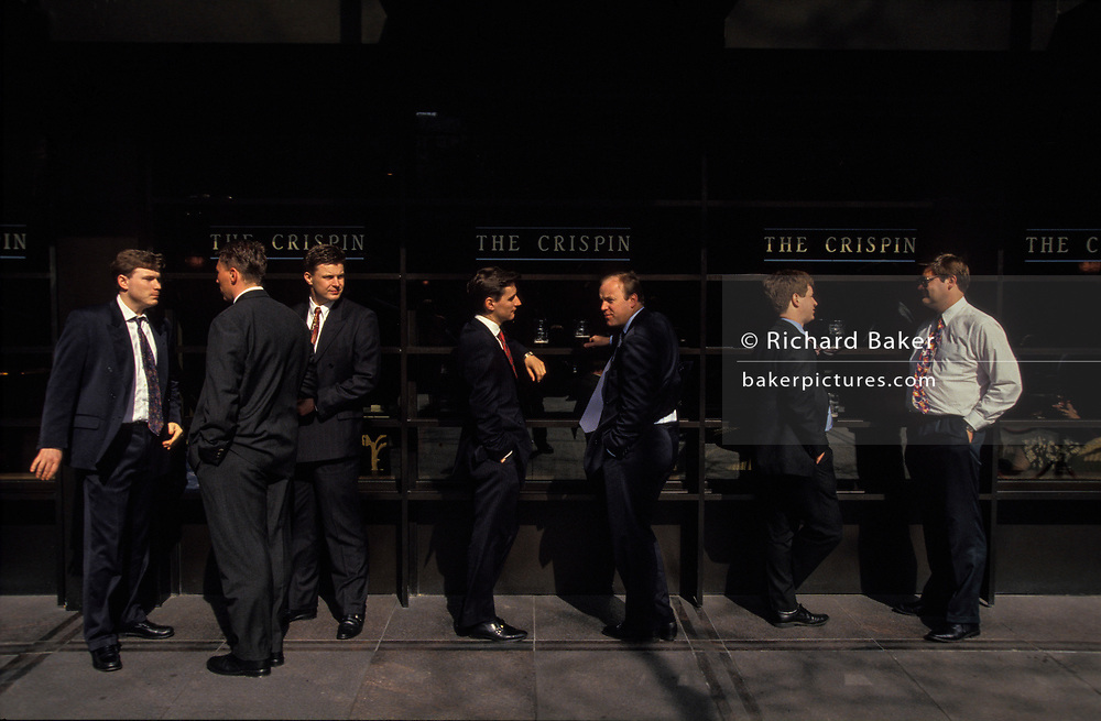 Seven City Businessmen stand drinking and smoking outside The Crispin, a pub in Broadgate, an Eighties development in the City of London, on 16th June 1993.