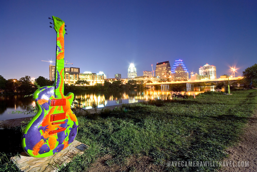 View of downtown Austin from Riverside, across Town Lake with one of the painted Austin City Limits guitars in the foreground. The guitar is on the southern bank of Town Lake and the shot is facing east.