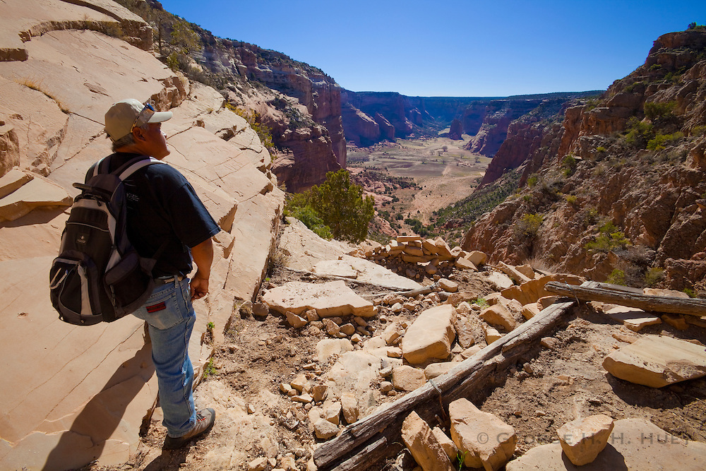 350109-1002 ~ Copyright: George H. H. Huey ~ James Yazzie, Navajo Indian guide and resident of Canyon de Chelly, hiking on the Twin Trails. Canyon de Chelly National Monument, Arizona.
