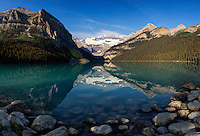 The early morning hours shine sunlight on emerald green Lake Louise in Banff National Park, Alberta, Canada