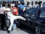 An anti-Aristide protester kicks the car carrying Kathy Huddleston, Charge d'Affairs for the U.S. Embassy, 11 October 1993, in Port-au-Prince, Haiti, after the car was not allowed entry to the sea port to welcome U.N. troops.  The protesters shouted that they would not allow an occupying force in their country.