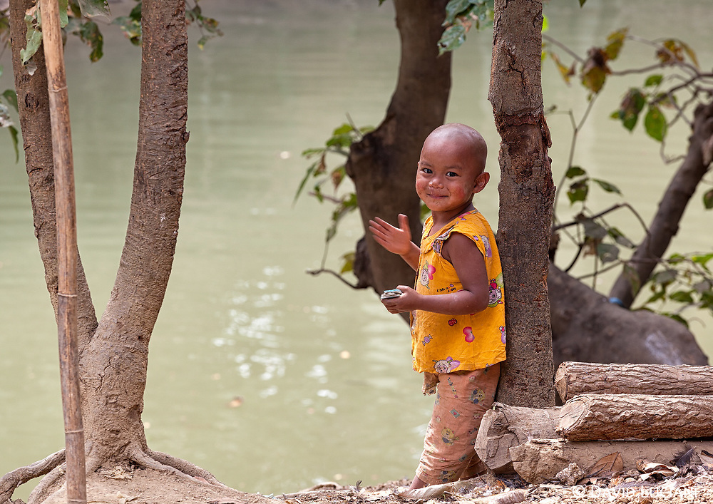 A boy standing near a small river in a settlement outside the center of Mrauk U.