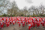 Arriving for teh start and the warm up - The London Santa Run 2015 in Battersea Park - 2,000 Santa's take part in an annual 'Red & White' bearded 'charge' around Battersea Park in a 6k festive charity fun run. The runners are of all ages and abilities and many run at a very slow pace but enjoy the event and the cause. The Santa Run is organised to raise funds for Disability Snowsport UK, a national charity helping people with disabilities to access the thrill of snowsports. The charity ensures that children and adults, with a range of disabilities (including cerebral palsy, Down's syndrome,  visual impairment and autism), can access programs across the UK to enable them to make friends, improve their confidence and have fun through a sport which they would otherwise be excluded from.