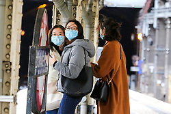 © Licensed to London News Pictures. 01/02/2020. London, UK. Women are seen on Paddington Station platform wearing face masks following the outbreak of Coronavirus in Wuhan, China. According to Twitter two people were taken to hospital from Paddington Station on the evening of Friday 31 January, amid fears that Coronavirus has speed to London. Part of the station was cordoned off following a woman sitting on a bench, while staff in face masks keep guard. Photo credit: Dinendra Haria/LNP  Photo credit: Dinendra Haria/LNP
