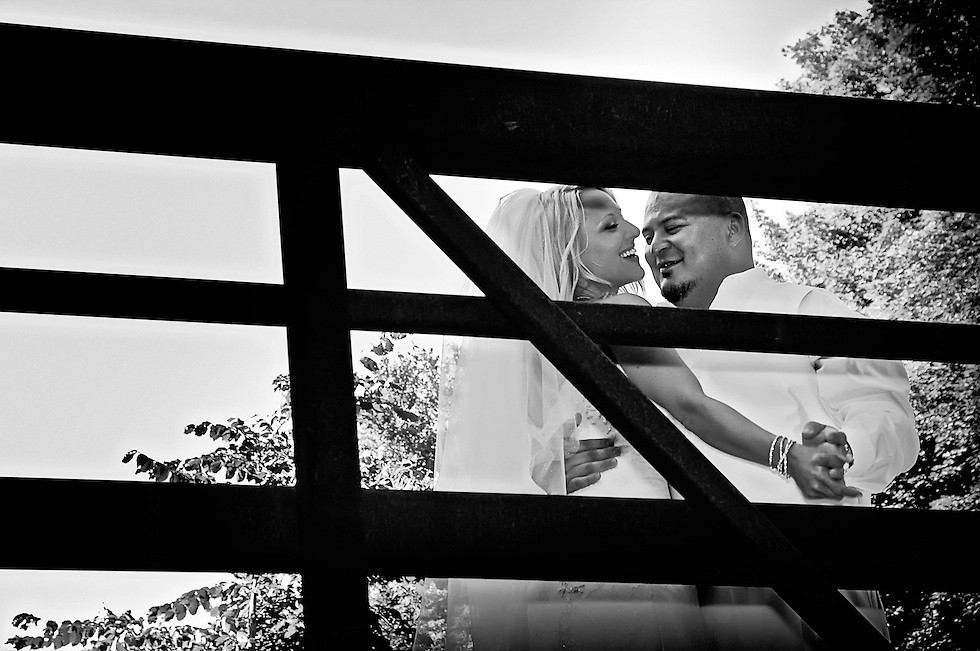 The newlyweds, Natasha and Marcelo, share a dance on the bridge at G. Ross Lord Park, Vaughn Ontario Canada. Photographer: Dean Oros, Images of a Promise.
