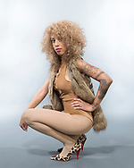 Female fashion model against a dark background posing in a brown one piece, fur vest and brown tights.