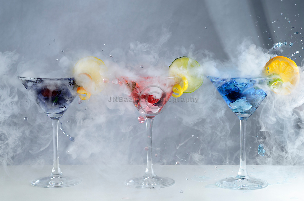 Smoking, splashing, colourful blue, pink and purple craft cocktails.