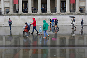 Pedestrians walk beneath the columned architecture of the National Gallery in Trafalgar Square, Westminster, on 9th April 2019, in London, England.