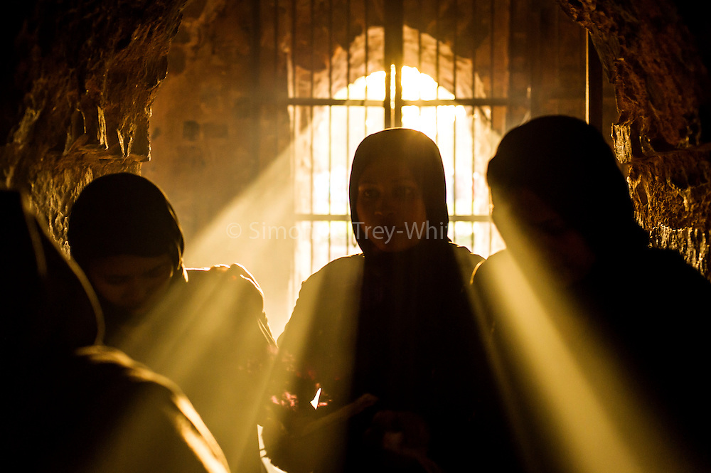 19th March 2015, New Delhi, India. Believers silhouetted against the light pass through an arched doorway in the ruins of Feroz Shah Kotla in New Delhi, India on the 19th March 2015<br /> <br /> PHOTOGRAPH BY AND COPYRIGHT OF SIMON DE TREY-WHITE a photographer in delhi<br /> + 91 98103 99809. Email: simon@simondetreywhite.com<br /> <br /> People have been coming to Firoz Shah Kotla to leave written notes and offerings for Djinns in the hopes of getting wishes granted since the late 1970's. Jinn, jann or djinn are supernatural creatures in Islamic mythology as well as pre-Islamic Arabian mythology. They are mentioned frequently in the Quran  and other Islamic texts and inhabit an unseen world called Djinnestan. In Islamic theology jinn are said to be creatures with free will, made from smokeless fire by Allah as humans were made of clay, among other things. According to the Quran, jinn have free will, and Iblis abused this freedom in front of Allah by refusing to bow to Adam when Allah ordered angels and jinn to do so. For disobeying Allah, Iblis was expelled from Paradise and called &quot;Shaytan&quot; (Satan).They are usually invisible to humans, but humans do appear clearly to jinn, as they can possess them. Like humans, jinn will also be judged on the Day of Judgment and will be sent to Paradise or Hell according to their deeds. Feroz Shah Tughlaq (r. 1351&ndash;88), the Sultan of Delhi, established the fortified city of Ferozabad in 1354, as the new capital of the Delhi Sultanate, and included in it the site of the present Feroz Shah Kotla. Kotla literally means fortress or citadel.