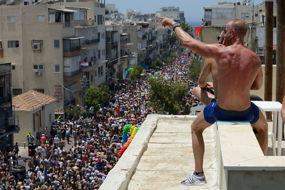 Men are watching from a roof at the annual gay pride parade in Tel Aviv, June 09, 2017. About 200,000 members of the Israeli and international gay community participated the annual gay pride parade in Tel Aviv. Photo by Gili Yaari