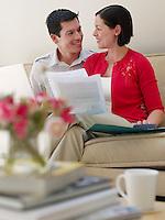 Couple using laptop  and holding documents sitting on sofa