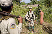Forest rangers check the legality of a house built within the reserves boundaries. The forest rangers are employed by the Ministry of Environment but sponsored by Flora and Fauna International who pays them 75% of their salary and provides training and accommodation. They undertake regular patrols in to the Samkos Wildlife Sancturary which is part of the Cardamom Mountains Nature Reserve looking for illegal activites such as logging, poaching, land encroachment and the production of the illegal substance sassafras oil. The Cardamom Mountains and surrounding forests is the largest and most pristine area of intact forest in SE Asia. Covering an area of 2.5 million acres it became one of the last strong holds of a retreating Khmer Rouge. Their presence helped preserve the forest as no-one dared to venture inside. But with the Khmer Rouge gone, it faces new dangers from poachers, loggers and illegal drug factories. In charge of protecting this vast forest are a handful of rangers who's job it is to track down and arrest those who are helping to destroy this delicate habitat.